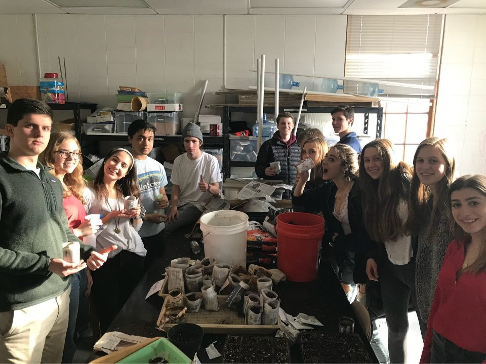 Environmental Club enjoys a brief break in the planting room. The club grows plants during the year and gives them away during Earth Week.