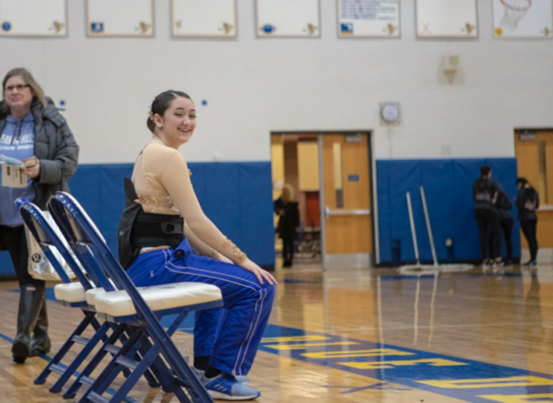 Marissa Giangorgi, then a junior, sits out during a competition. Sidelined by a back injury, she helped coach the team as they advanced to Nationals.