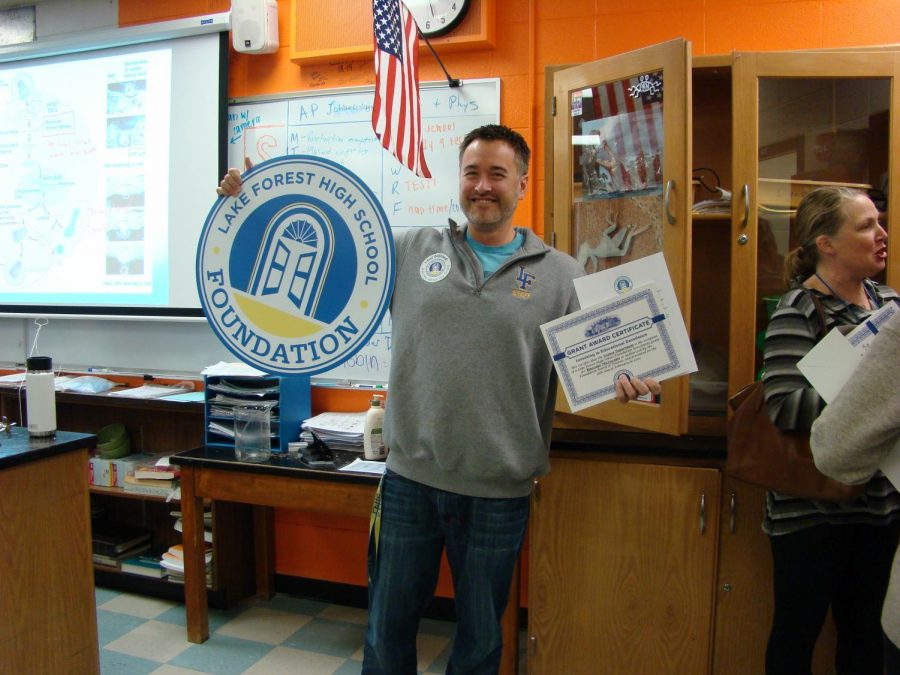 Mr. Schuessler celebrates receiving a grant award certificate for new microscopes.