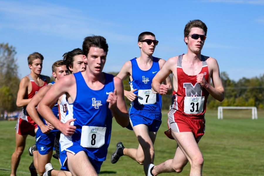Nate Schmitt and Ben Rosa running at the North Suburban Conference Cross Country meet in October.